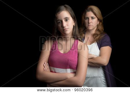 Teenage girl and her mother sad and angry at each other isolated on black