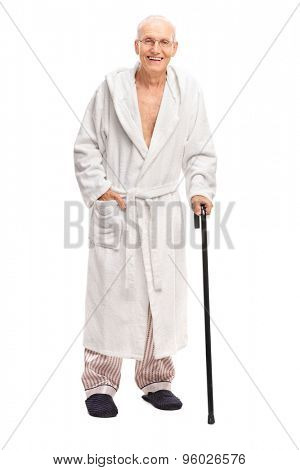 Full length portrait of a senior man in a bathrobe holding a cane and looking at the camera isolated on white background