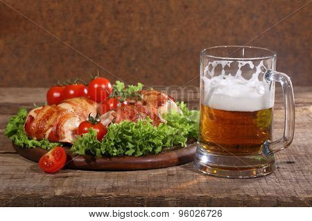 Beer In A Transparent Mug And Chicken Beaters In Bacon Submitted With Greens, Bread And Tomatoes On