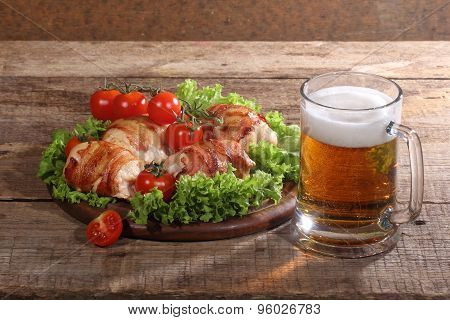 Beer In A Transparent Mug And Chicken Beaters In Bacon On A Wooden Table