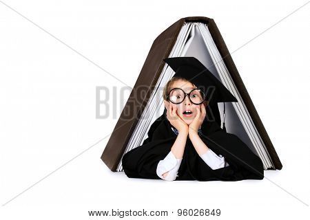 Cute student boy in graduation suit lying under the huge book. Educational concept. Isolated over white.