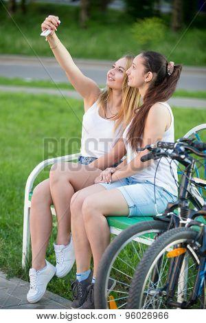 Cute Young Biker Women Taking Self Portrait In Park