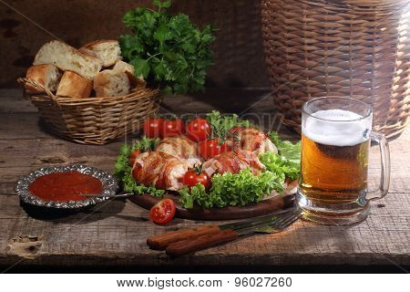 Chicken Beaters In Bacon Submitted On Leaves Of Salad With Fresh Tomatoes And Beer In A Transparent