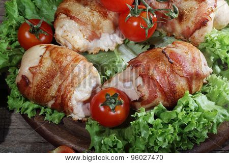 Chicken Beaters In Bacon Submitted On Leaves Of Salad With Fresh Tomatoes