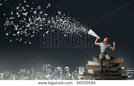 Young man in bow tie screaming in paper trumpet