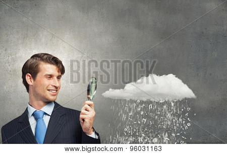 Businessman in suit looking through magnifying glass