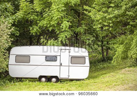 Old Camping Trailer Standing In Woods On Summer Day.