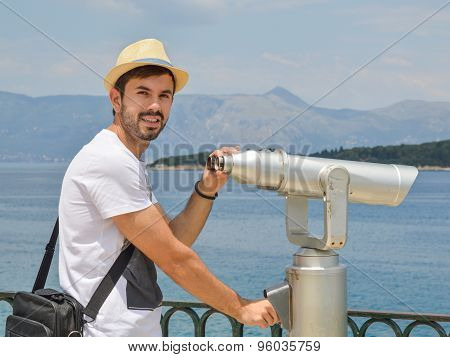 Young Man Holding Public Binoculars At The Seaside Wearing Straw Hat