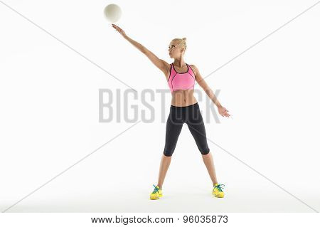 Rhythmic gymnast doing exercise with ball in studio.