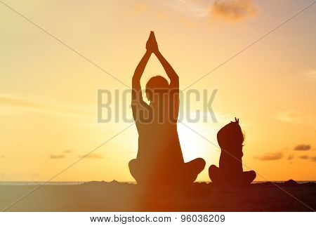 father and little daughter doing yoga at sunset