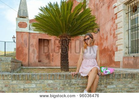 Girl Sitting On A Wall With Colorful Background