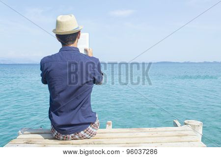 Young Man Sitting On The Dock Reading A Book