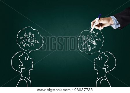 Close up of hand drawing dialogue between two on blackboard