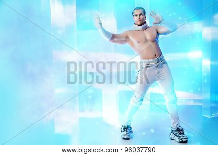 Technologies of the future, man of the future. Handsome muscular man with futuristic make-up stands on a luminous transparent background and touches something virtual.