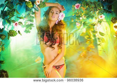 Beautiful brunette woman in bikini among tropical plants. Beauty, fashion. Spa, healthcare. Tropical vacation.