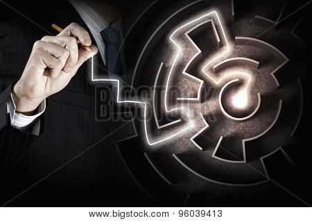 Close up of businessman drawing way out of labyrinth