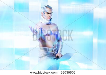 Handsome muscular man with futuristic make-up wearing glasses working on a laptop and touches something virtual. Technologies of the future.