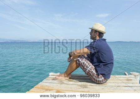 Young Man Sitting On The Dock Looking At Blue Sea