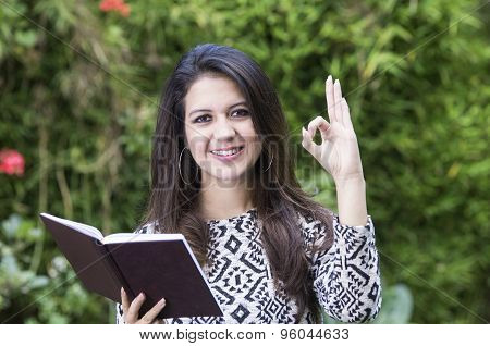 Hispanic brunette business woman in park environment wearing formal clothing holding book open while
