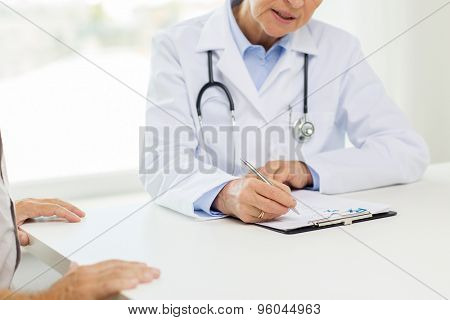 medicine, age, health care and people concept - close up of senior female doctor with clipboard and patient at hospital