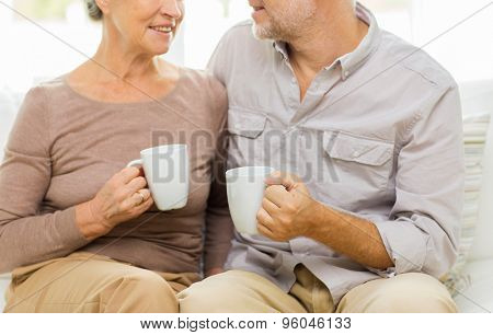 family, relations, age, drinks and people concept - close up of happy senior couple with cups hugging on sofa at home