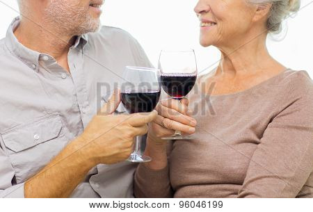 family, holidays, drinks, age and people concept - close up of happy senior couple clinking glasses with red wine at home
