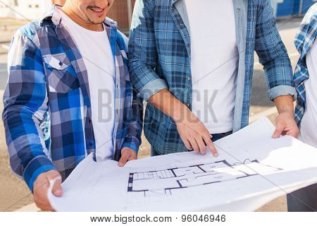 building, construction, development, teamwork and people concept - close up of two smiling builders with blueprint outdoors