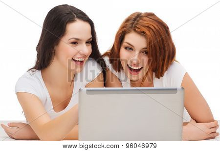 technology, internet and entertainment concept - two smiling teenage girls in white t-shirts with laptop computer