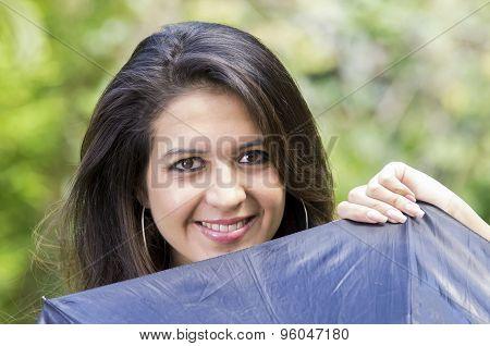 Closeup good-looking hispanic brunette woman head peeking up from behind black umbrella smiling to c