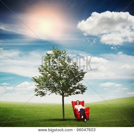 smiley businesswoman resting in red chair on green meadow near tree against blue sky