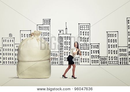 funny woman in formal wear pulling big bag over drawing city