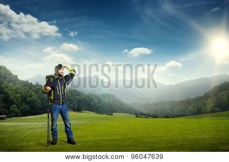 smiley hiker with backpack and hiking poles looking forward at beautiful nature