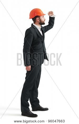 serious man in formal wear and orange hardhat looking into the distance. isolated on white background