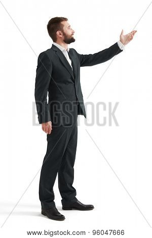 full length portrait of businessman in formal wear pointing hand at something and looking at it. isolated on white background