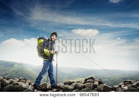 smiley hiker in full equipment walking on stones against beautiful background with hills and sky