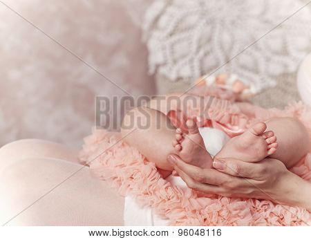 Mother Holding Feet Of Her First Child.