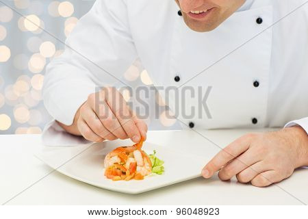 cooking, profession, haute cuisine, food and people concept - close up of happy male chef cook decorating dish over holidays lights background