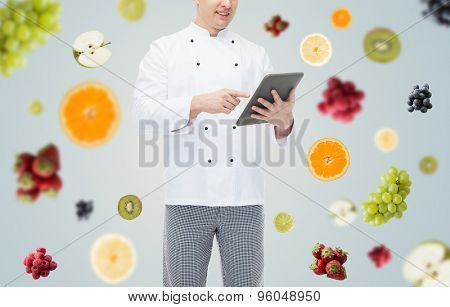 cooking, profession and people concept - close up of happy male chef cook holding tablet pc computer over fruits and berries on gray background
