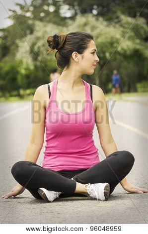 Hispanic brunette in yoga clothing sitting with legs crossed and arms down touching ground while loo