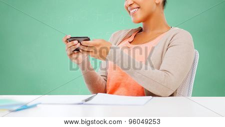 education, school, people and learning concept - smiling african woman with smartphone in office over green chalk board background