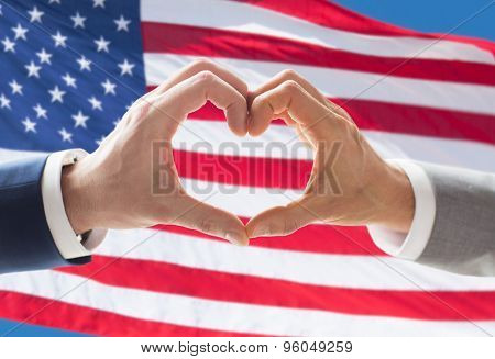 people, homosexuality, same-sex marriage, gesture and love concept - close up of happy male gay couple hands showing heart hand sign over american flag background