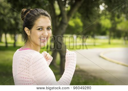 Hispanic brunette model in park wearing white top caption of upper body sideways angle smiling to ca