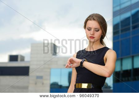 Business Woman Looks Thoughtfully At Her Wristwatch
