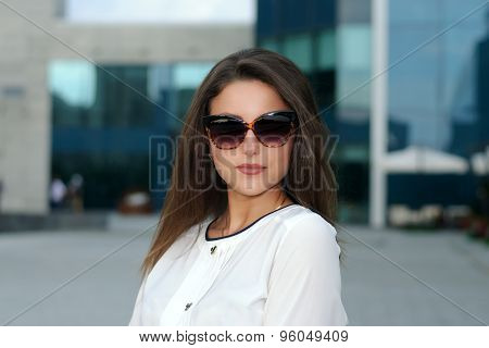 Business Female Is On The City's Business District In Sunglasses