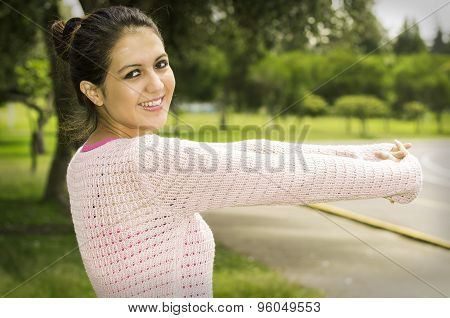 Hispanic brunette wearing yoga clothing in park environment standing on grass stretching arms forwar