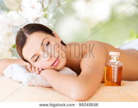 spa, beauty, people and body care concept - happy woman lying on the massage desk over green natural background