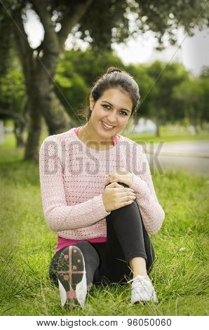 Hispanic brunette sitting on grass in yoga clothing left knee bent with arms wrapped around looking