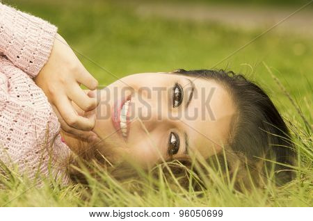 Headshot hispanic female brunette model with head resting on grass and looking sideways towards came