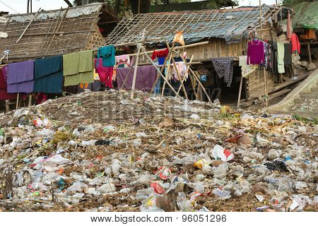 Laundry drying under a large rubbish pile in a slum area in Mandalay, Myanmar