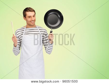 people, cooking and culinary concept - happy man or cook in apron with frying pan and wooden spoon over green natural background